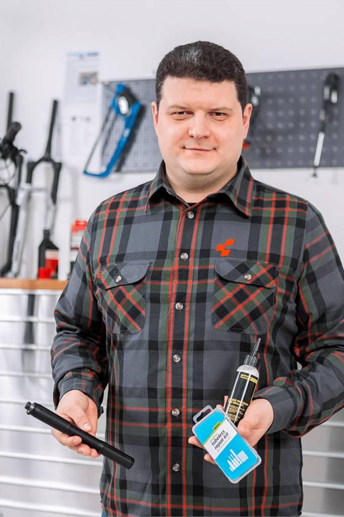 Unser Machaniker zeigt Reifendichtmittel, ein Tubeless-Reparatur-Kit und eine Flexible Minipumpe