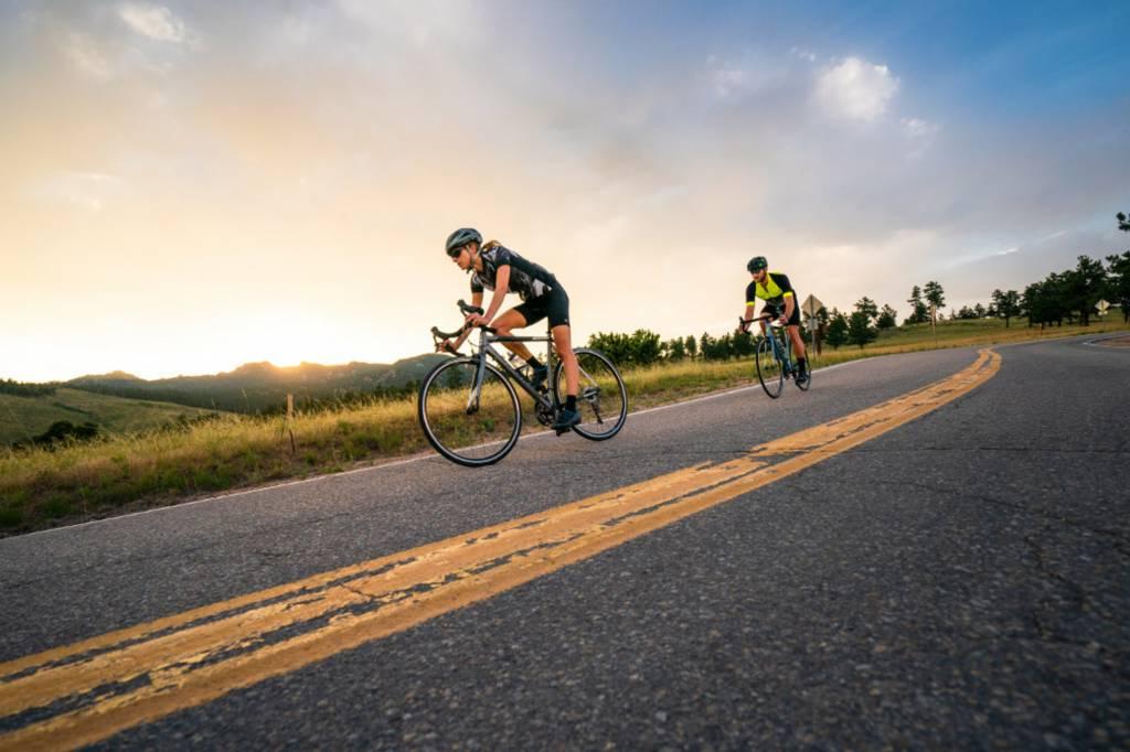 Zwei Rennradfahrer*innen im Sonnenaufgang