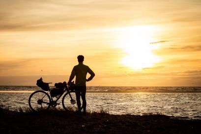 Bikepackingrad am Meer im Sonnenuntergang